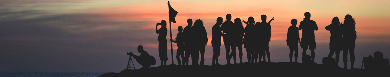 Über uns: Man sieht eine Gruppe von Menschen, die den Sonnenuntergang anschauen.
