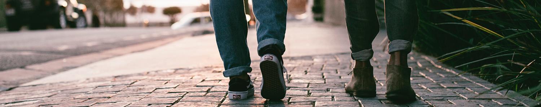 Man sieht zwei Menschen auf dem Gehweg laufen. Der Gehweg ist gepflastert. Die Beine sind auf dem Bild abgeschnitten, so dass man nur die Füße bis zum Knie der zwei Menschen sieht.