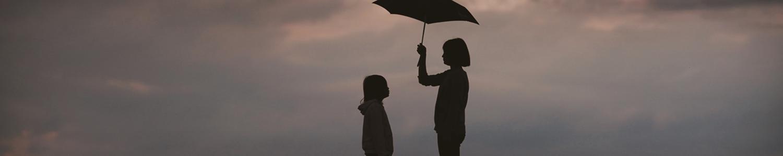 Hilfe Angebote: Eine Frau hält den Schirm über ein Mädchen, damit es nicht nass wird, da es vermutlich anfängt zu regnen.