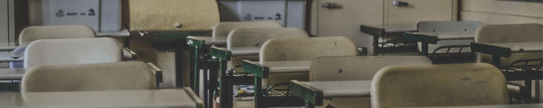 Man sieht einen Ausschnitt aus einem Klassenraum. Zu sehen sind nicht besetzte Stühle und Tische aus der Perspektive eine/r Lehrer*in.