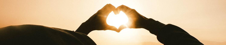 Man sieht eine Person von hinten, die mit ihren zwei Händen ein Herz formt und dieses in die Sonne hält.