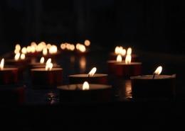 Es ist komplett dunkel und man sieht nur einige brennenden Kerzen, die Licht in das Dunkel bringen.