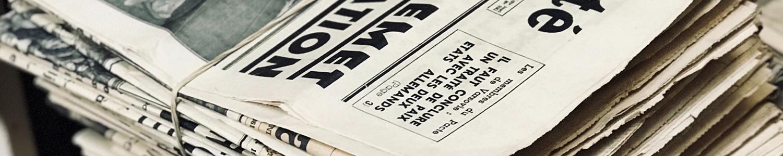 Mehrere Zeitungen, die aufeinander liegen.